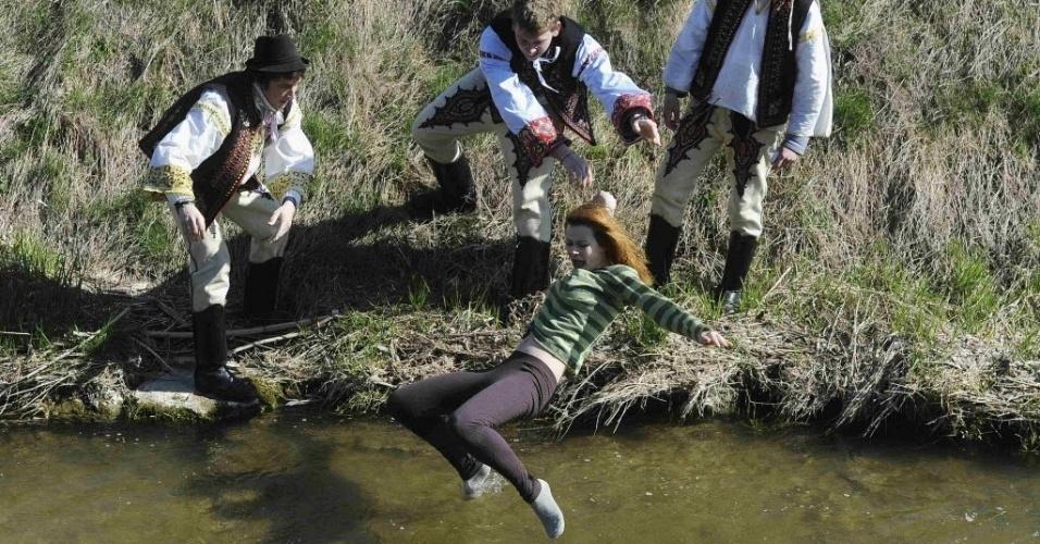 Jovens vestindo roupas tradicionais jogam garota em lago durante comemorações da Páscoa na Eslováquia na segunda-feira (9). É costume no país molhar e chicotear garotas, o que se crê assegurar sua fertilidade e beleza