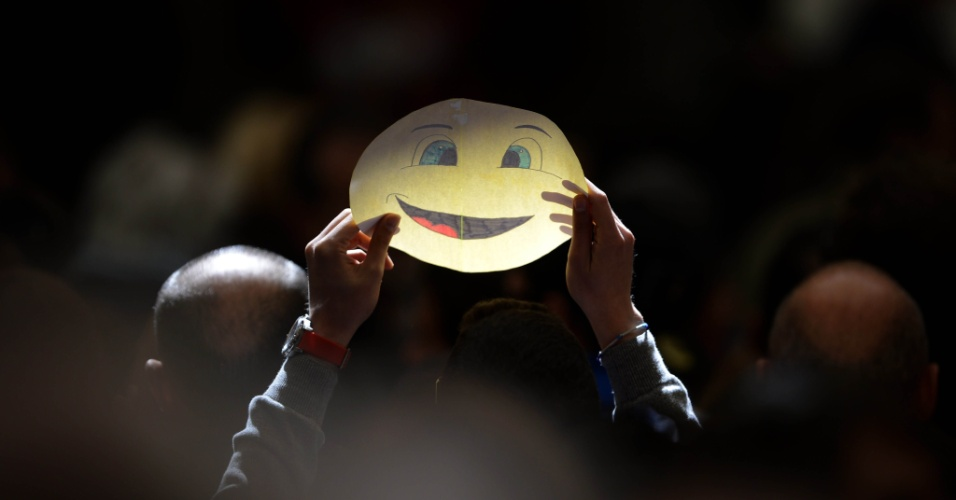 Peregrinos com banners de rosto sorrindo durante a oração do Papa Bento XVI no pátio Regina Coeli, em Roma