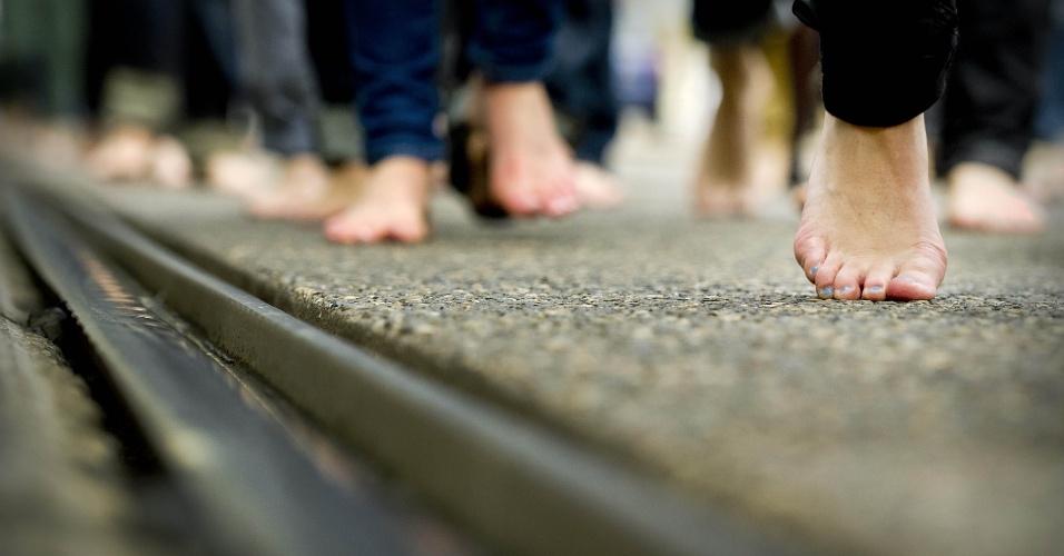 Participantes do evento um dia sem sapatos, andam descalços através do centro de Amesterdã