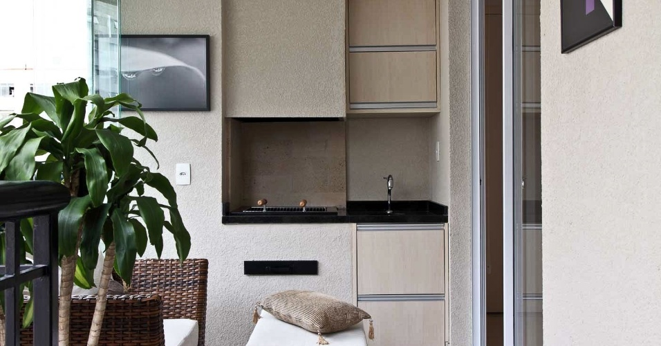 A varanda do apartamento Putti tem churrasqueira e pia de apoio feita com a mesma marcenaria da cozinha (laminado melamínico); os móveis, rústicos, são de fibra de madeira, comprados na Fibra Móveis. Os interiores são assinados por Flavio Castro