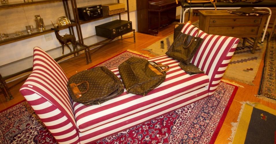 10.abr.2012 - Sofá listrado e bolsa e bolsas da marca Louis Vuitton que pertenciam a Clodovil. As peças serão leiloadas nesta quinta-feira (12) e têm lance livre