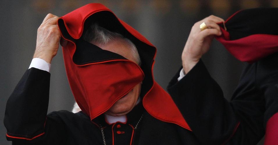 Cardeal ajusta seu manto durante a audiência geral do Papa Bento XVI na Praça de São Pedro no Vaticano