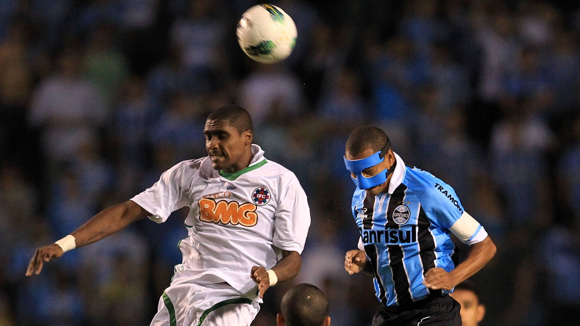 De máscara após quebrar o nariz, Gilberto Silva, do Grêmio, disputa a bola com Cláudio Luiz, do Ipatinga