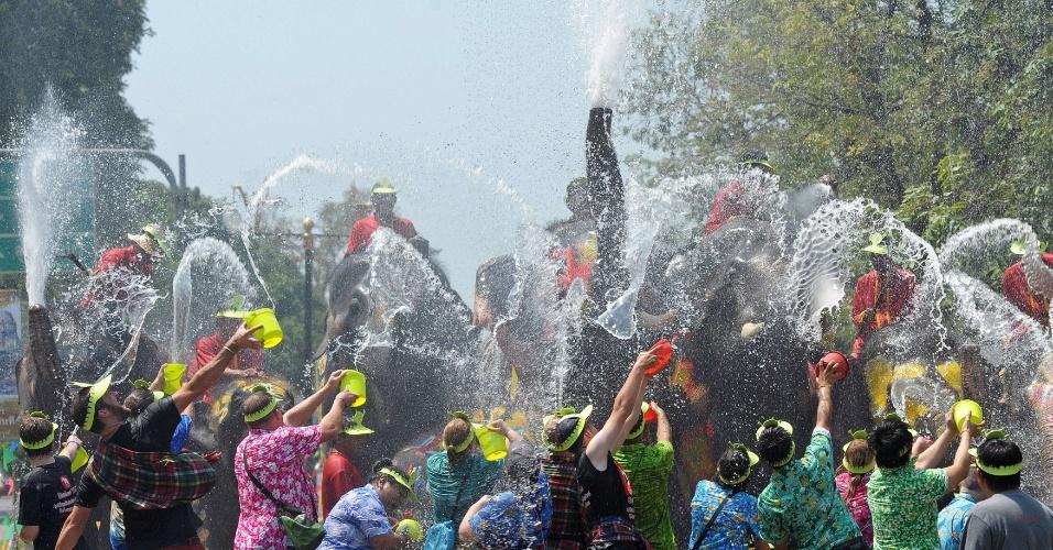 Elefantes espirram água em turistas durante o Festival Songkran, em Ayutthaya, na Tailândia