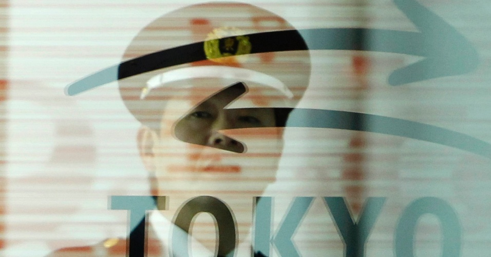 Guarda de segurança é visto através de um logotipo na Bolsa de Valores de Tóquio