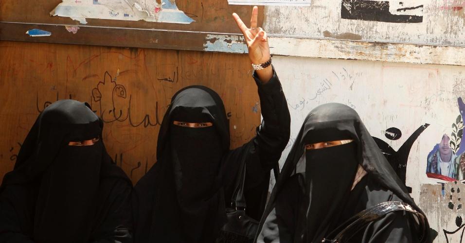 Mulher faz sinal de vitória na praça Taghyeer, em Sanaa, capital do Iêmen, local em que manifestantes contrários ao governo nacional acampam há mais de um ano