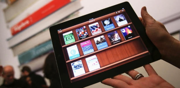 Mulher segura iPad que exibe o aplicativo iTunes U, que permite acesso a conteúdos acadêmicos