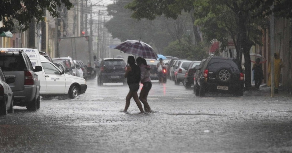 Mulheres atravessam a rua Jaraguá, no Bom Retiro, centro de São Paulo. A via ficou alagada  após forte chuva