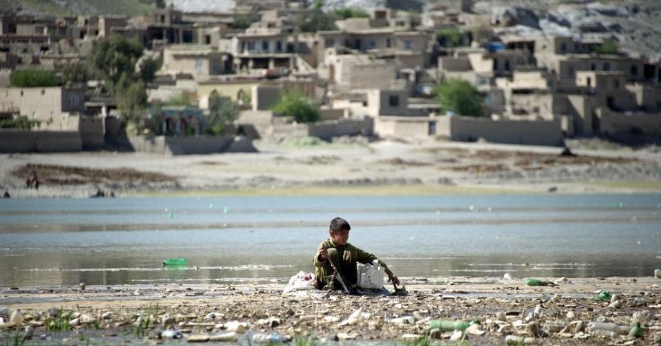 Apoiado em pneu, jovem pesca peixes em rio poluído no rio Cabul, no Afeganistão