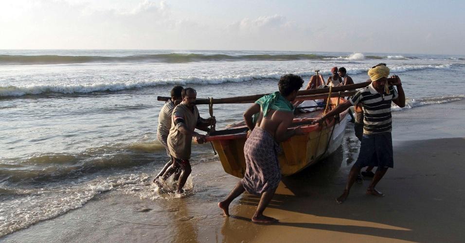 Homens arrastam barco para praia após pescaria na praia de Marina, em Chennai, na Índia