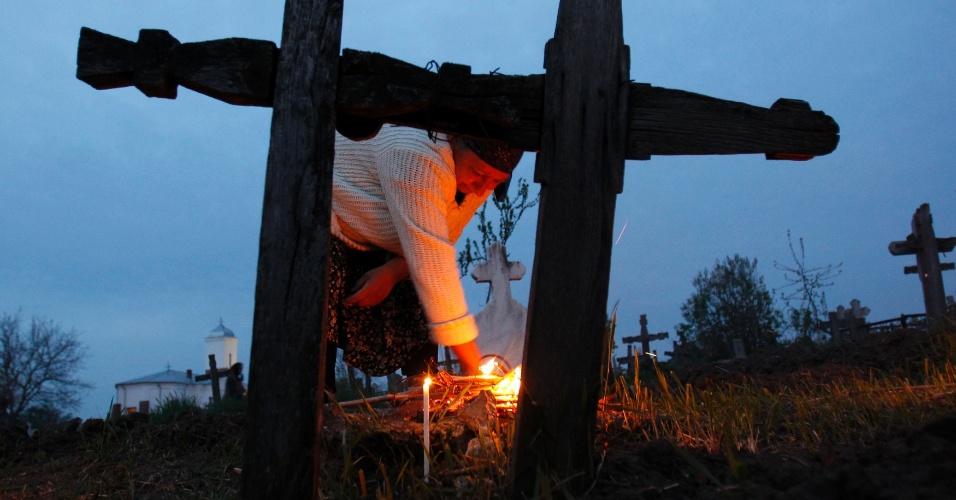 Mulher acende velas em frente a sepultura de parentes em cemitério do vilarejo de Copaciu, na Romênia