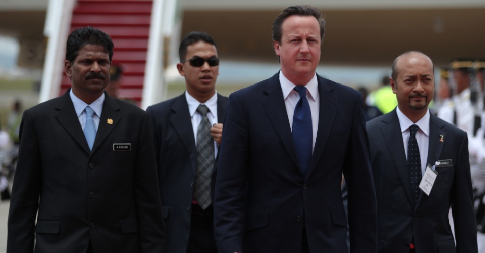 O primeiro-ministro britânico, David Cameron (centro), é acompanhado pelo vice-ministro das Relações Exteriores malaio, A. Kohilan (esquerda), em sua chegada ao Aeroporto Internacional Kuala Lumpur, em Sepang, na Malásia
