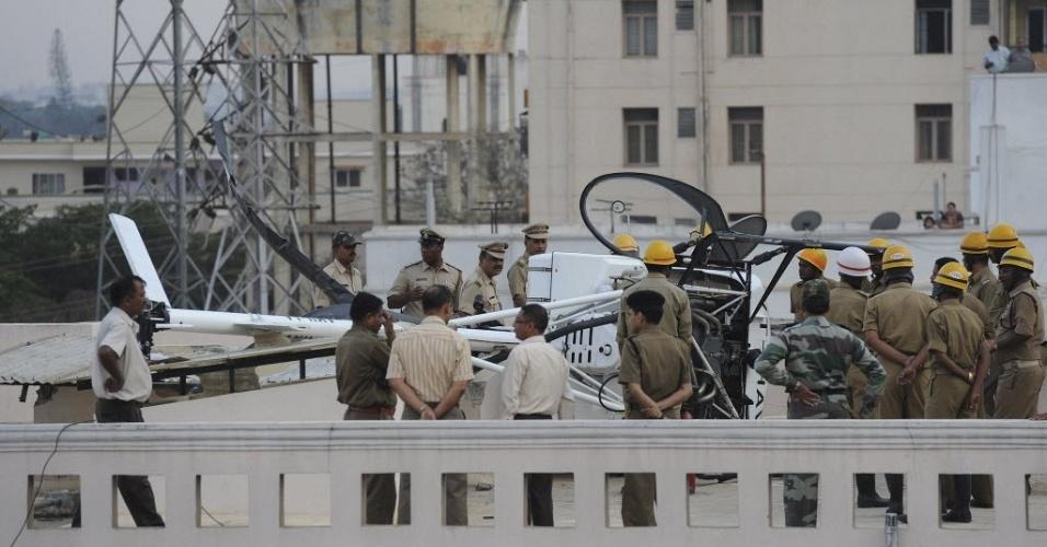 Policiais, bombeiros e oficiais da Aeronáutica da Índia socorrem helicóptero que fez um pouso de emergência em telhado de prédio residencial de Bangalore. Não há informações de feridos ou danos