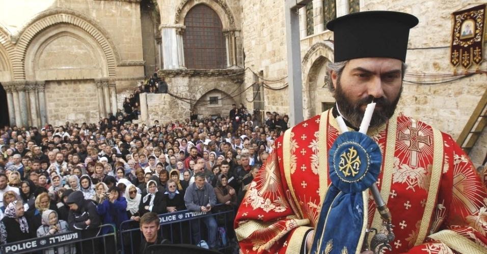Público observa membro do clérigo ortodoxo durante Ofício do Lava-pés do lado de fora do Santo Sepulcro, na Cidade Antiga de Jerusalém. O ritual é parte das comemorações da Páscoa ortodoxa, celebrada no próximo domingo (15)