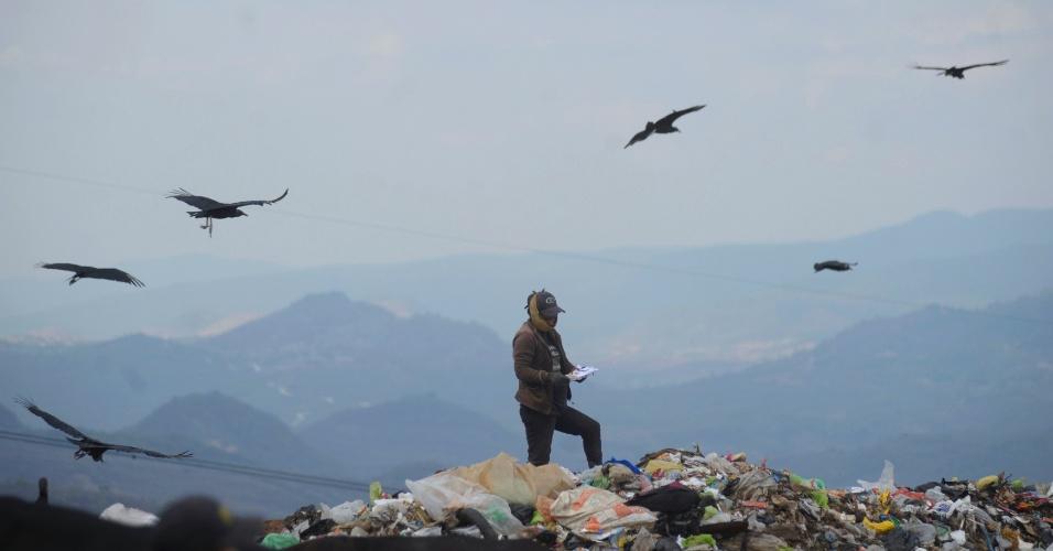 Coletor de lixo para reciclagem lê papel em meio a lixão municipal em Tegucigalpa (Honduras)