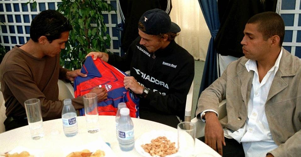 Giovanni (e) e Sonny Anderson (d) entregam camisa do Barcelona ao tenista Gustavo Kuerten (14/04/1998)