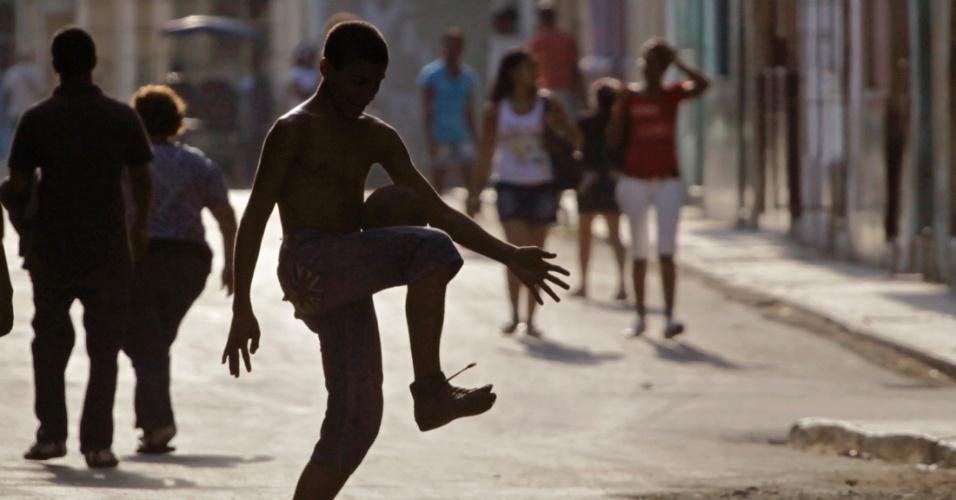 Menino brinca com bola em rua de Havana, em Cuba