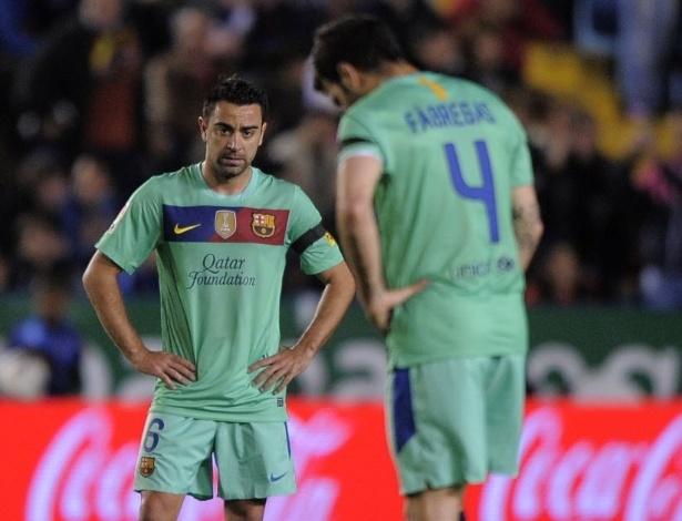 Xavi e Fábregas de semblante fechado, ao dar a saída de bola, após gol do Levante