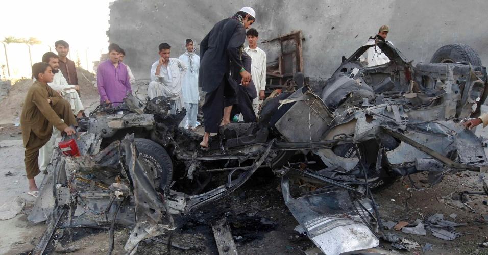 Afegãos observam destroços de carro usado em ataque suicida na província de Jalalabad, neste domingo (15). Insurgentes do Taleban lançaram uma série de ataques coordenados no Afeganistão