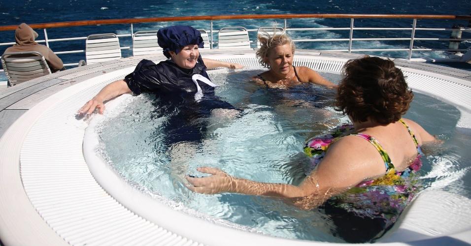 As americanas Debbie Pennington (esquerda) e Cindy Tulloch (so seu lado esquerdo) aproveitam ofurô no deck do cruzeiro que refaz o caminho do Titanic, navio que afundou há 100 anos