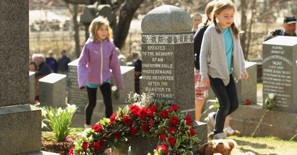 Crianças caminham próximo de túmulo de uma criança que morreu no naufrágio do Titanic e não foi identificada. O cemitério Fairview Lawn (no Canadá) abriga 121 pessoas que morreram no navio que afundou no dia 14 de abril de 1912