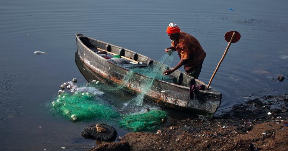 Pescador limpa a rede após captura de peixes na madrugada deste domingo (25) em Karachi, no Paquistão