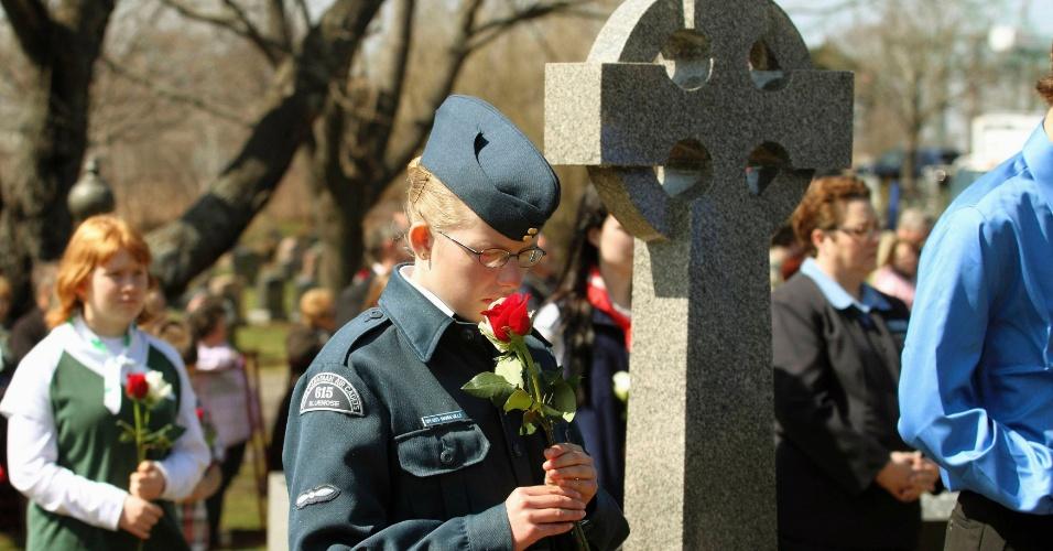 Sharon Spears-Mandeville, líder dos cadetes aéreos do Canadá, segura uma flor antes de colocar no túmulo de umas das vítimas do Titanic em Halifax, Nova Scotia (Canadá). No dia 14 de abril, uma série de celebrações relembraram os 100 anos de naufrágio do navio Titanic
