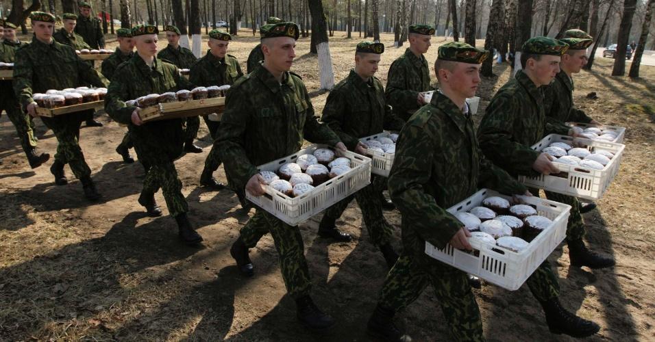 Soldados do Ministério do Interior de Belarus carregam bolos após missa da Páscoa ortodoxa em base militar perto da vila de Okolitsa, cerca de 30 km a leste de Minsk
