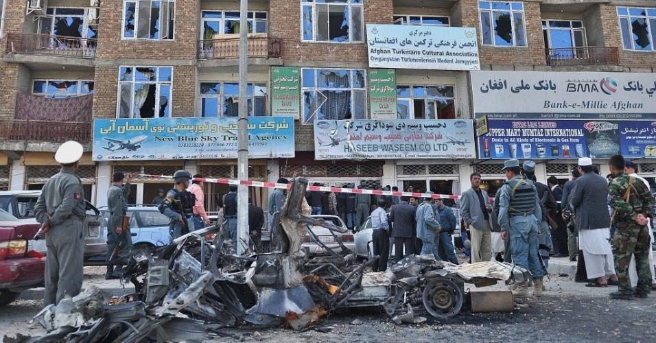 Agentes de segurança observam destroços de veículo usado em ataque suicida em Cabul, capital do Afeganistão. Nesta segunda-feira (16), o governo afirma que retomou controle da capital após 18 horas de confrontos com militantes talebans