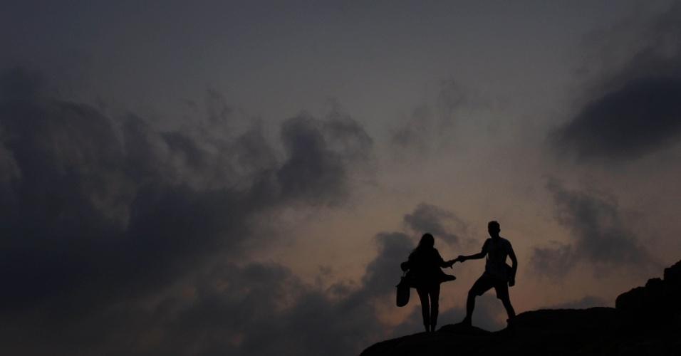 Casal passeia ao longo de algumas rochas perto de uma praia em Hong Kong