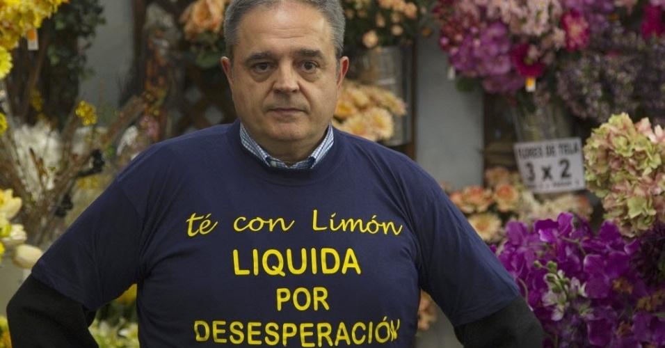 """Cesar Calle, 53, é um dos empresários que terá de fechar sua loja devido à crise financeira que assola a Espanha. Dono da loja Té com Limón, em Madri, ele usa camiseta onde se lê """"liquida por desespero"""""""