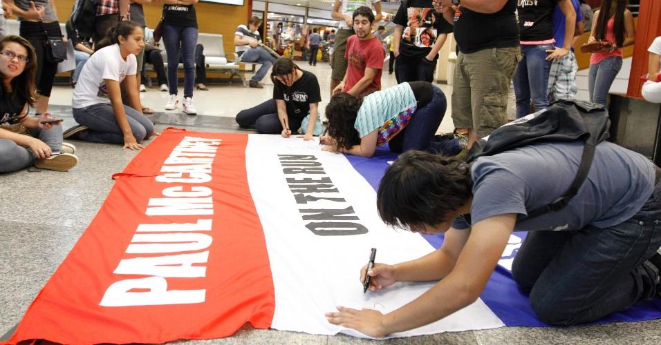 Fãs paraguaios escrevem em bandeira com as cores nacionais antes da chegada de Paul McCartney ao aeroporto Silvio Petirossi, em Luque