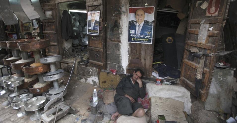 Homem aguarda clientes em sua loja em Sanaee, capital do Iêmen, tendo ao fundo pôsteres do presidente Abd-Rabbu Mansour Hadi