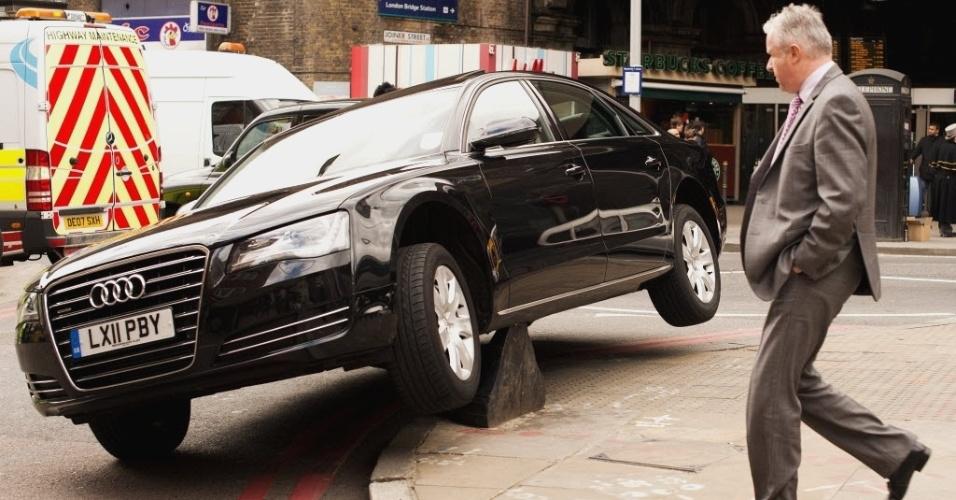 Homem observa carro que subiu em poste próximo a estação de trem de Londres