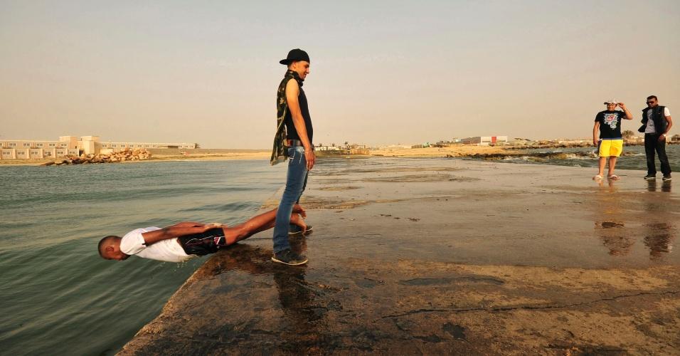 Jovem mergulha no mar Mediterrâneo na costa de Benghazi, na Líbia