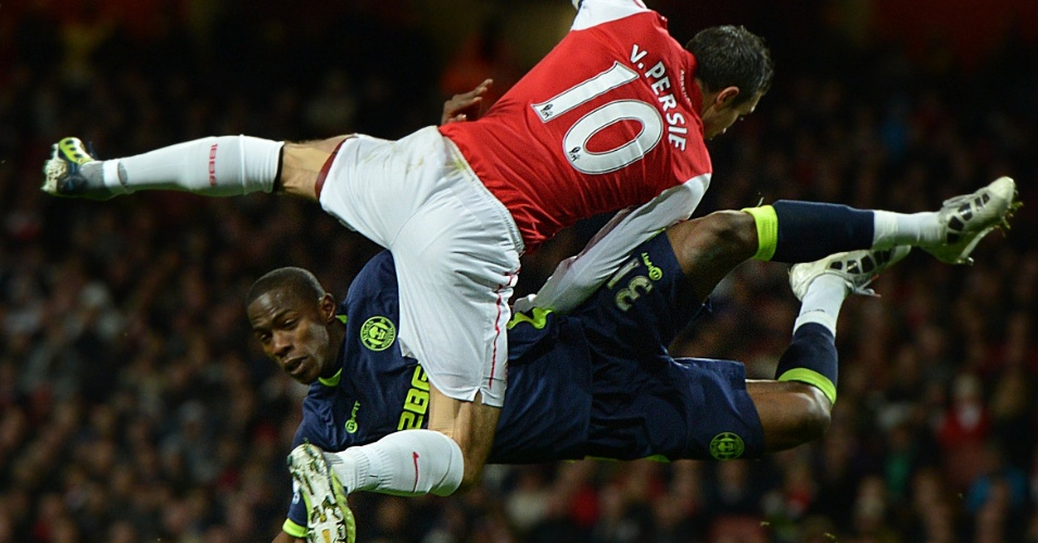 Maynor Figueroa (uniforme azul), do Wigan, e Robin van Persie, do Arsenal, disputam lance durante partida pelo Campeonato Inglês