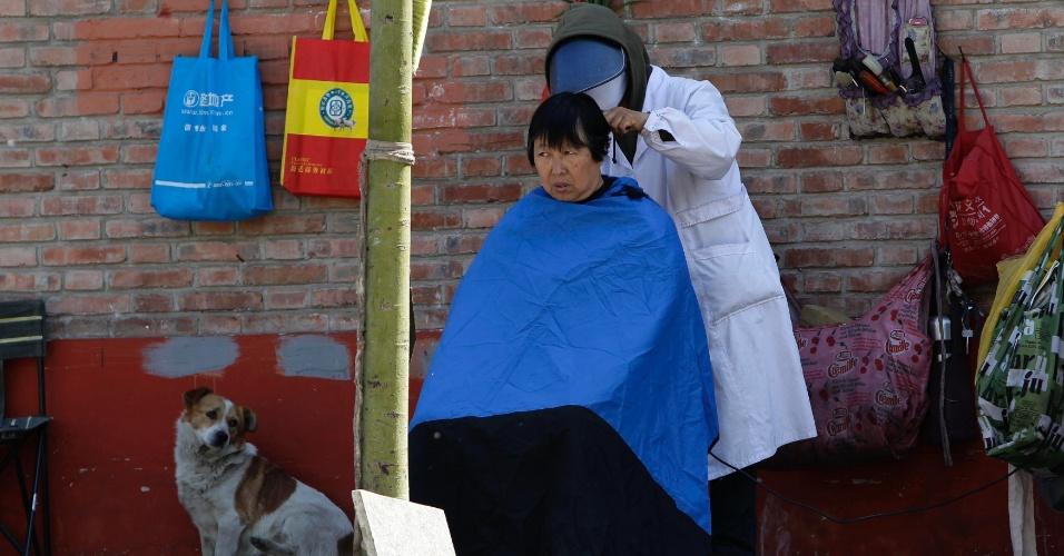 Mulher corta o cabelo em rua do centro de Pequim, na China