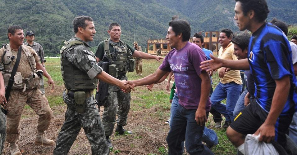 O presidente do Peru, Ollanta Humala (segundo, da esquerda para a direita), usando uniforme militar, cumprimenta residentes de vilarejo da província de La Convención, após visitar funcionários da empresa sueca Skanska e de outra companhia peruana que foram sequestrados na última semana no sudeste do Peru e libertados no sábado (15)