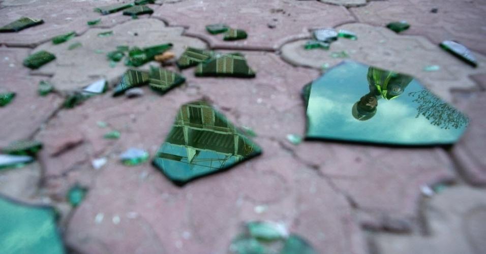 Policial afegão aparece em reflexo de vidro de janela quebrada em Cabul, capital do Afeganistão. Nesta segunda-feira (16), o governo afirma que retomou controle da capital após 18 horas de confrontos com militantes talebans