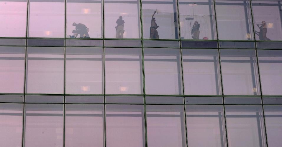 Trabalhadores limpam janelas em edifício de Moscou, na Rússia