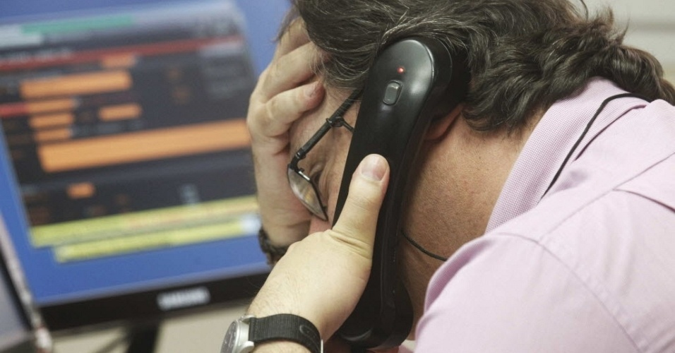 """""""Day trader"""" fala ao telefone durante leilão de títulos do Tesouro da Espanha em Madri. Nesta terça-feira, o Banco da Espanha disse que a economia do país voltou a cair na recessão dois anos após sair desta situação"""