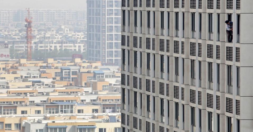 Homem limpa janela de complexo residencial recém-construído em Pequim, na China