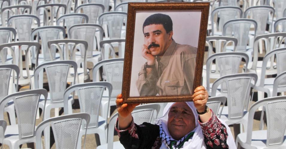 Homem mostra fotografia de seu filho mantido preso por Israel durante protesto em Hebron, na Cisjordânia