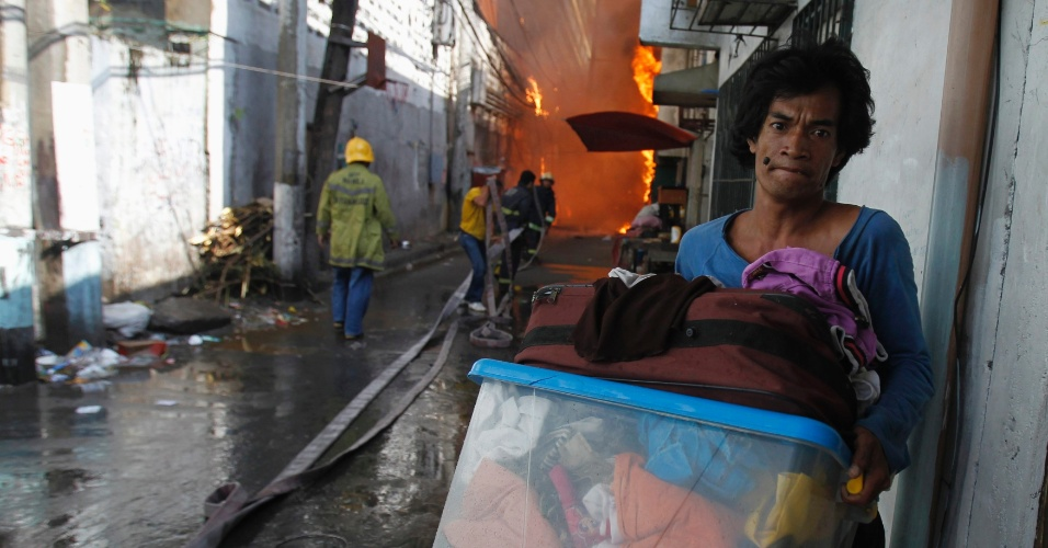 Homem carrega seus pertences enquanto bombeiros tentam controlar o fogo que destruiu estabelecimento comerciais e prédios residenciais em Manila, nas Filipinas
