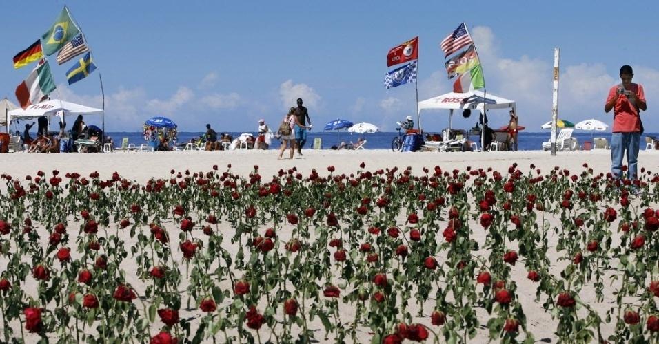 Turista registra imagem de jardim com 1300 rosas vermelhas colocadas pela ONG Rio de Paz nas areia de  Copacabana, zona sul do Rio de Janeiro. O ato faz tributo a vítimas de violência na cidade