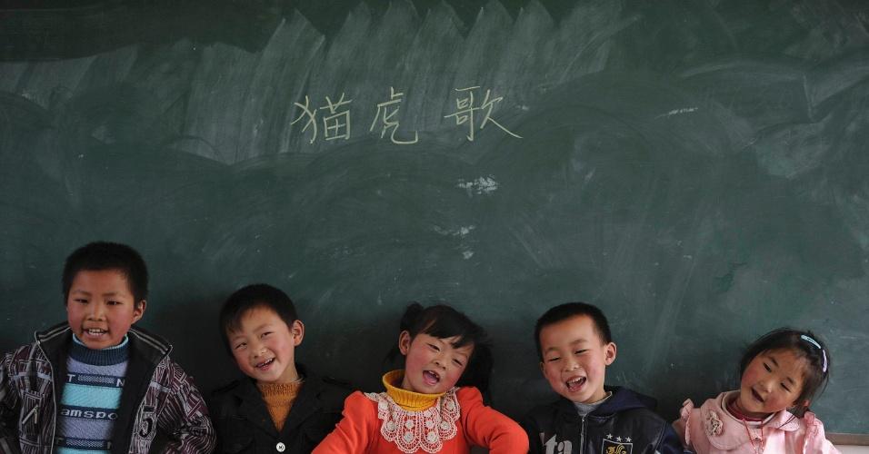 Alunos em frente de um quadro negro enquanto cantam uma música durante a aula em escola primária na vila Yuexi, em Anhui