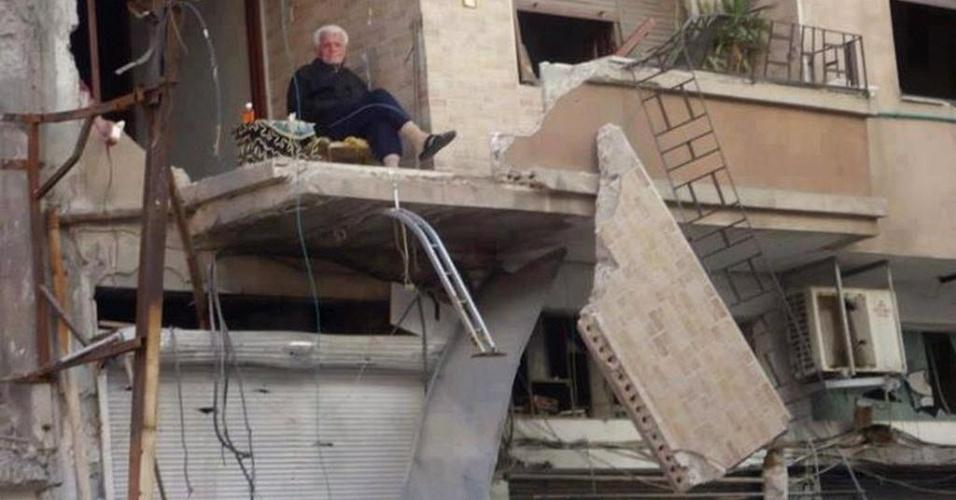 Homem se senta na varanda em ruínas de sua casa em Homs (Síria)