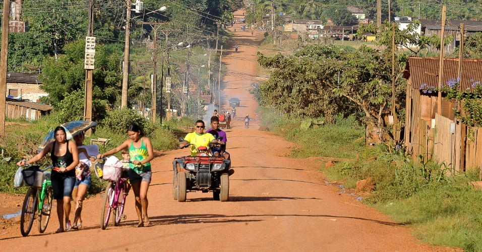 Moradores de Altamira, no Pará, caminham em rua sem calçamento que com a Rodovia Transamazônica
