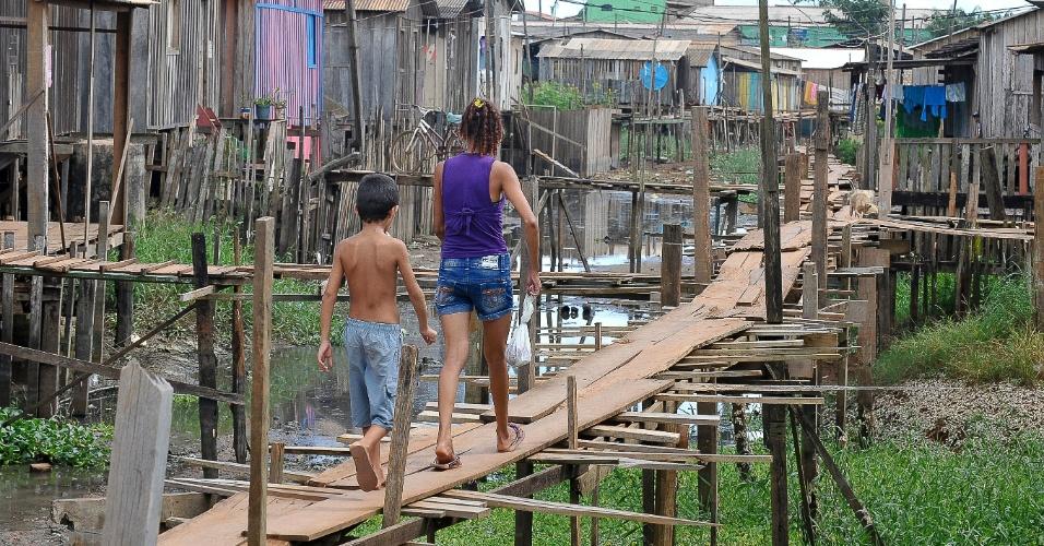 Moradores equilibram-se em ruas improvisadas com madeira em meio à falta de saneamento em Altamira, no Pará