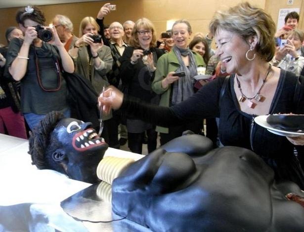 """O bolo nesta foto do dia 15 de abril tem causado controvérsia na Suécia. Seu criador, o artista Makode Linde, é a boca do bolo, e grita quando pedaços da """"genitália"""" do bolo são cortados. A minista da Cultura sueca, Lena Adelsohn-Liljeroth, que aparece sorridente e oferecendo um pedaço de bolo nesta foto, foi acusada de racismo e sofre pressão para renunciar"""